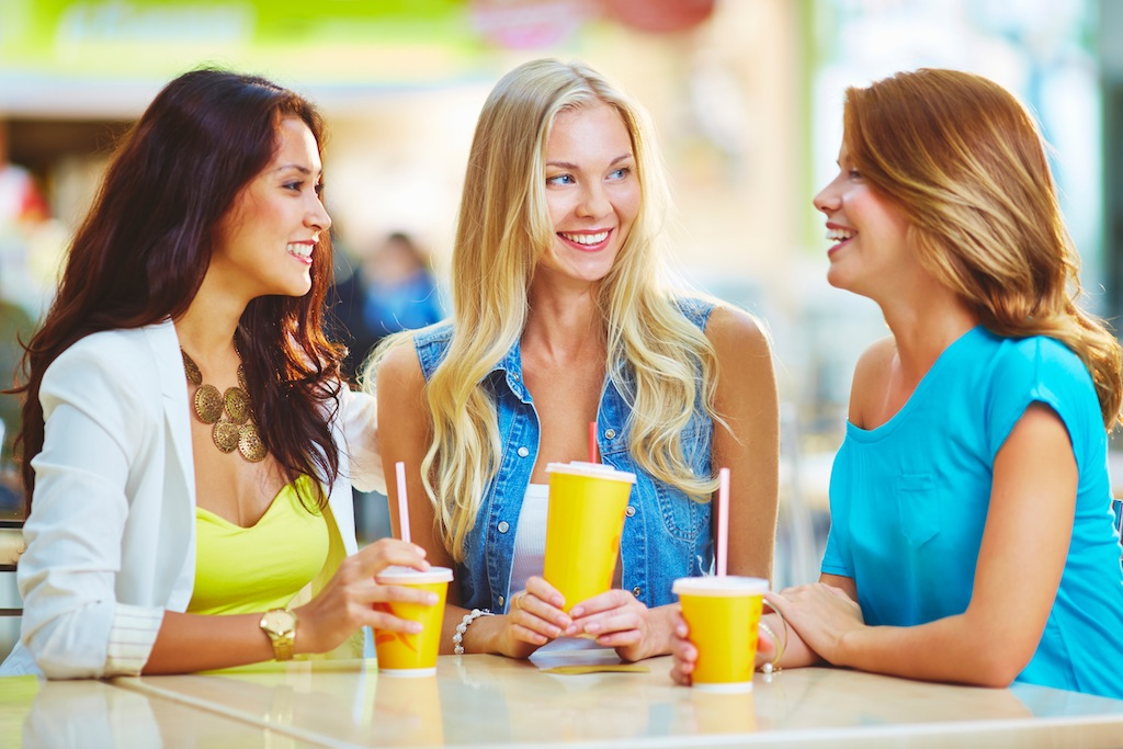 Portrait of three happy girls having drink while discussing their shopping