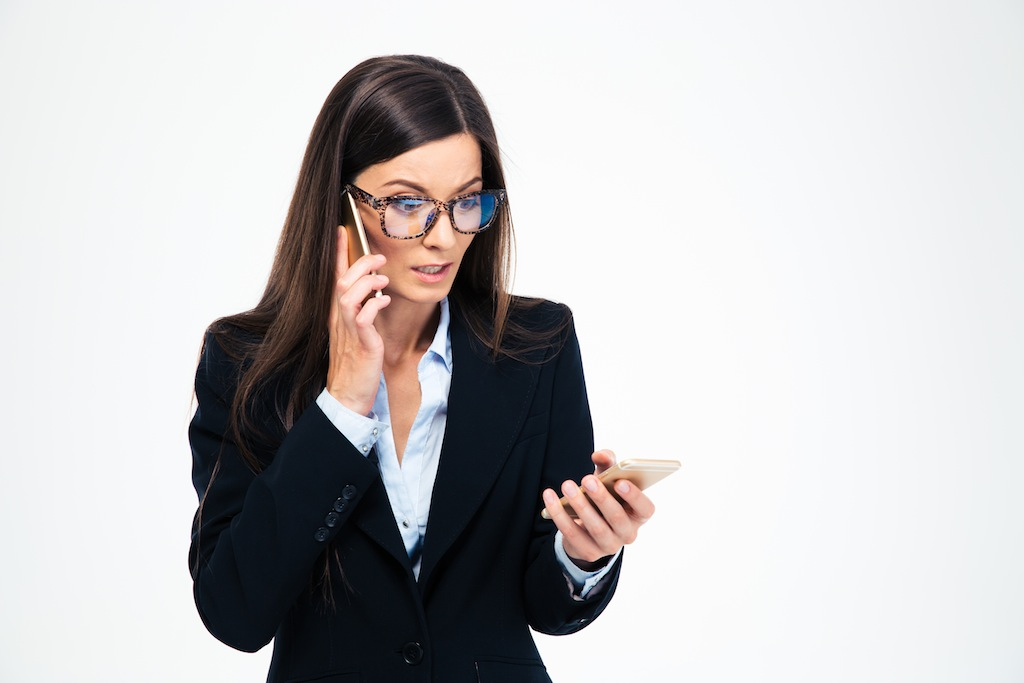 Stressed businesswoman talking on the phone isolated on a white background