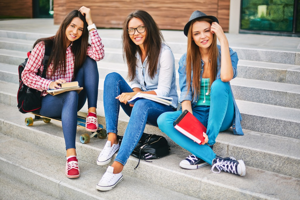 Portrait of happy teen girls looking at camera on stairs of college