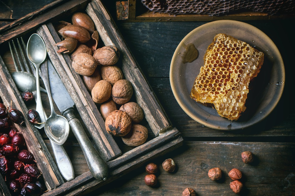 Fresh honeycomb with mix of nuts, briar and vintage cutlery over old wooden table. Top view.