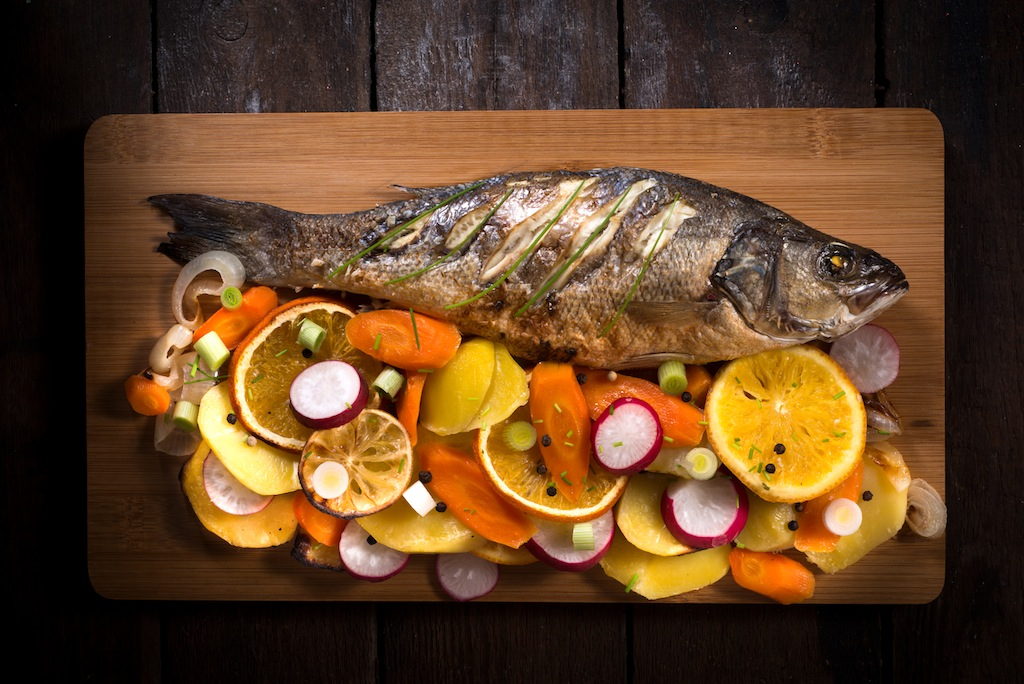 Prepared Bass fish with vegetables and fruit from above on wooden background
