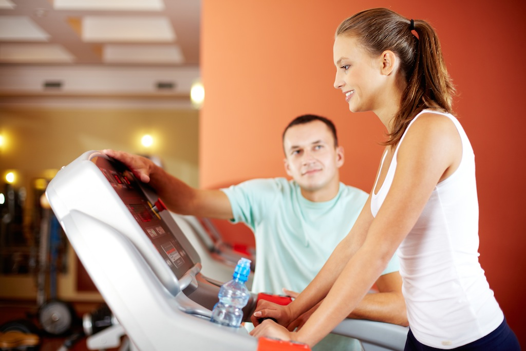 Young woman training in fitness club with instructor