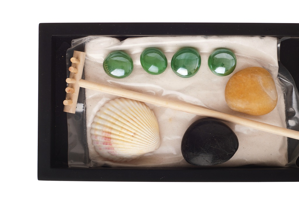gorgeous spa setting with stones, sand, seashell and rake on a black tray (close up picture isolated on white background)