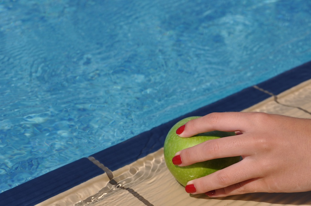 woman holding a green apple at the pool side as a diet concept
