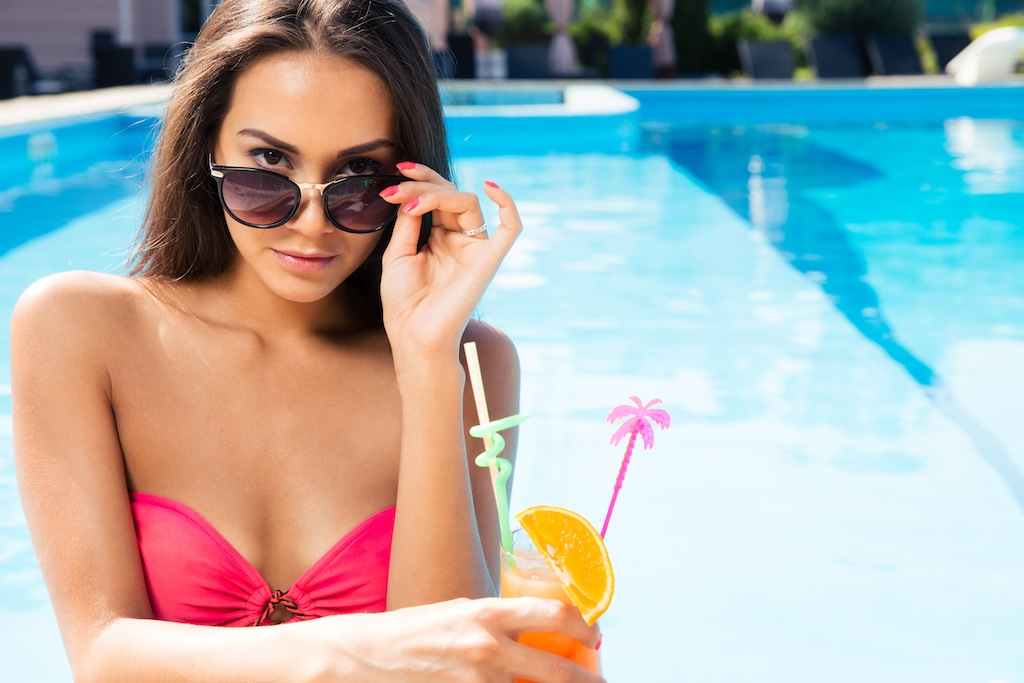 Portrait of a beautiful young woman holding cocktail in swim pool outdoors
