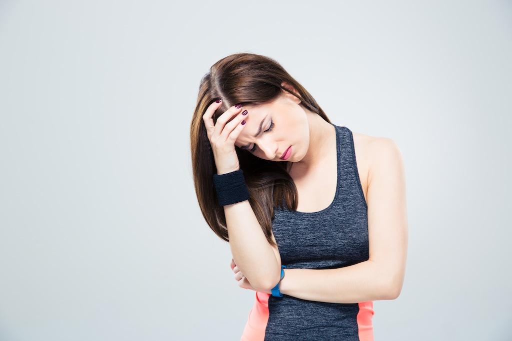 Fitness woman having headache over gray background