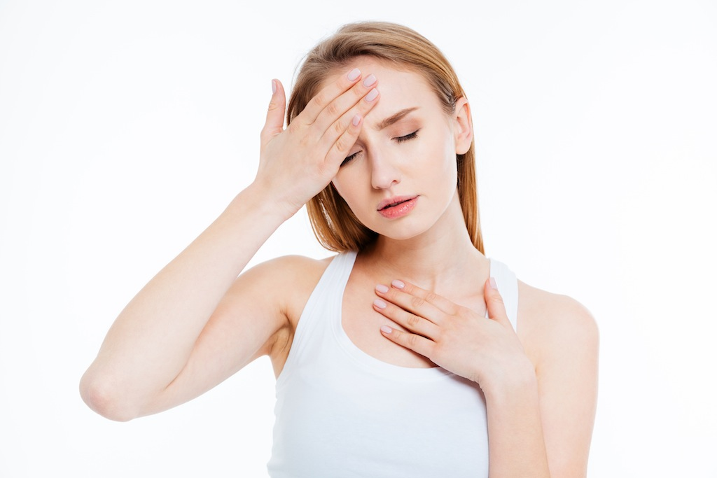 Sick woman touching her head isolated on a white background
