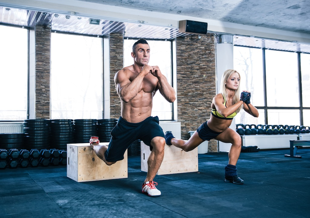 Woman and man working out with fit box at gym