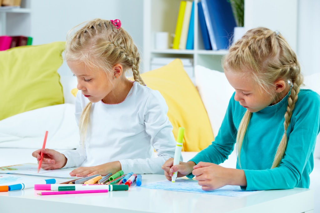 Portrait of twin girls drawing at home