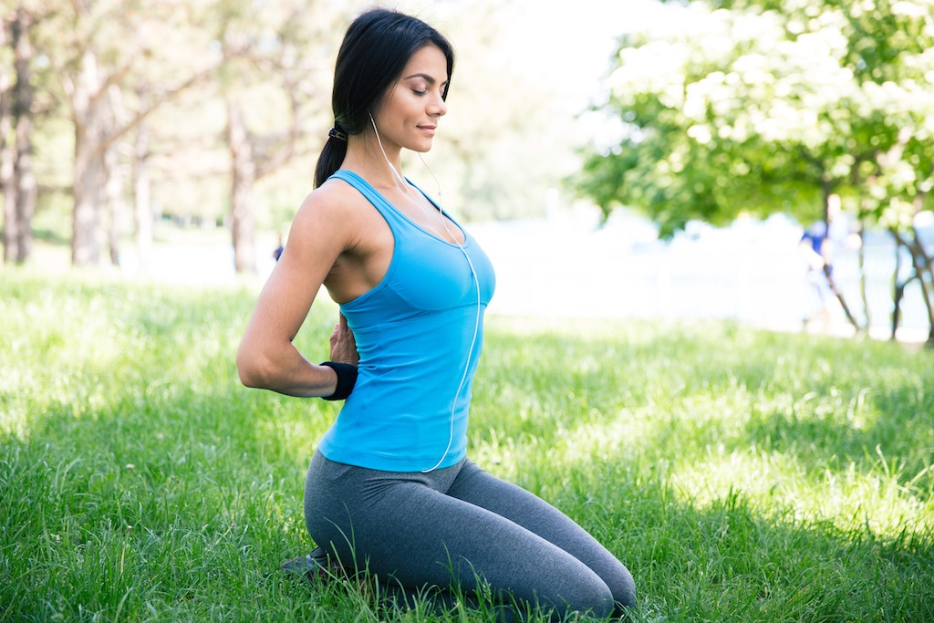 Fitness happy woman meditating on the green grass in park