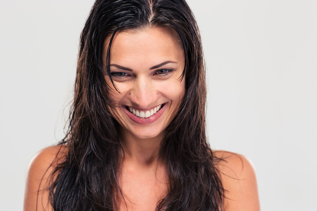 Portrait of a happy cute woman with wet hair isolated on a white background