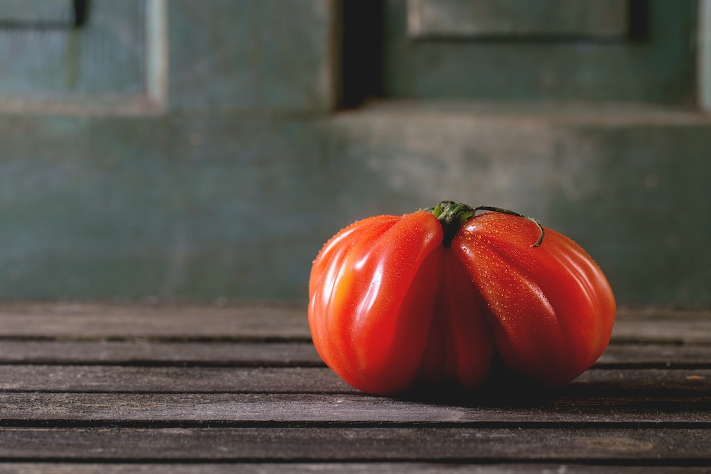 One big red tomato RAF over old wooden table. Dark rustic atmosphere