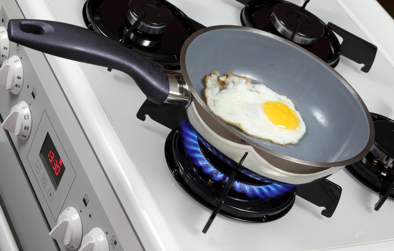 Fried egg cooking on a gas stove.