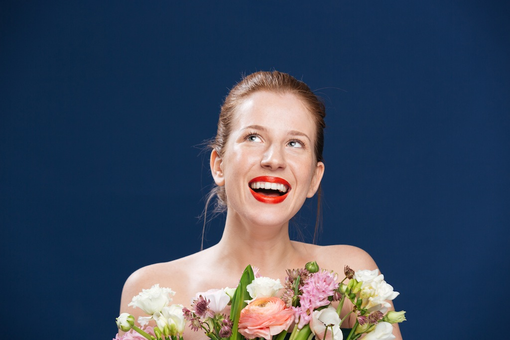 Laughing woman holding flowers and looking up over blue background