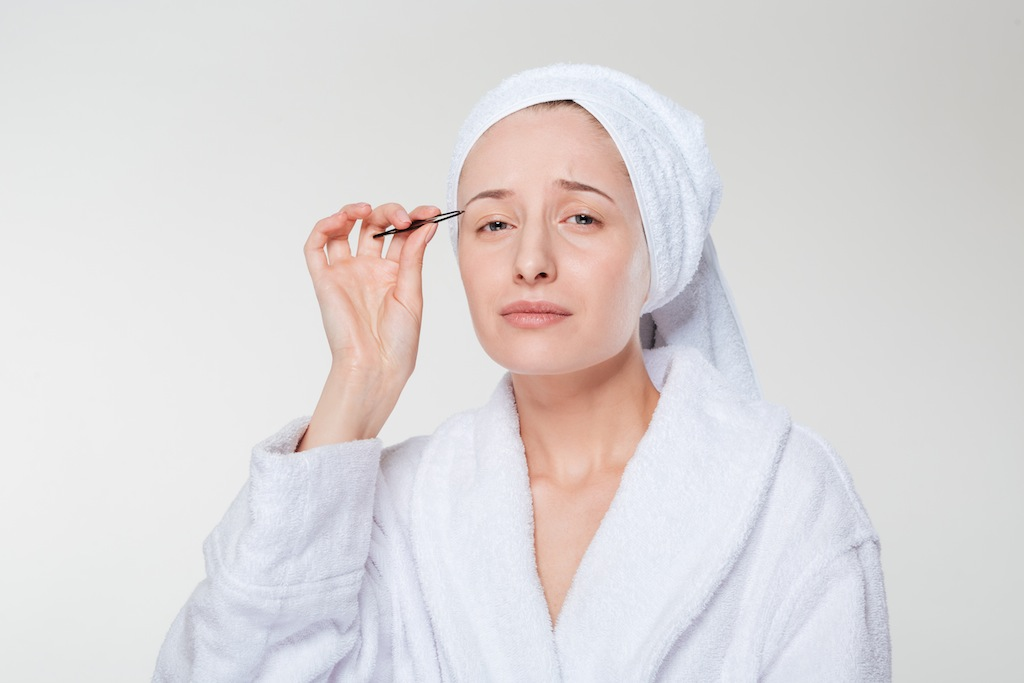 Woman in bathrobe and towel depilating her eyebrow on a white isolated background