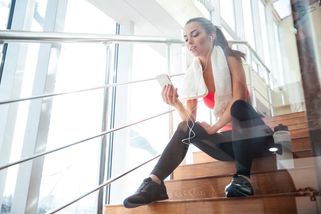 Sensual attractive woman athlete using mobile phone sitting on stairs in gym