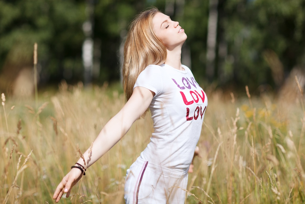 An attractive young girl falling in love standing in a crop field with her arms outstretched and eyes closed enjoying freetime