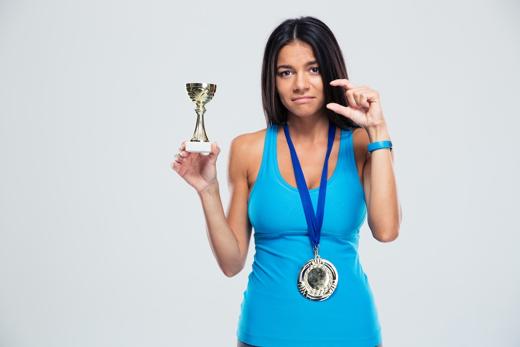 Sports success woman with medal over gray background