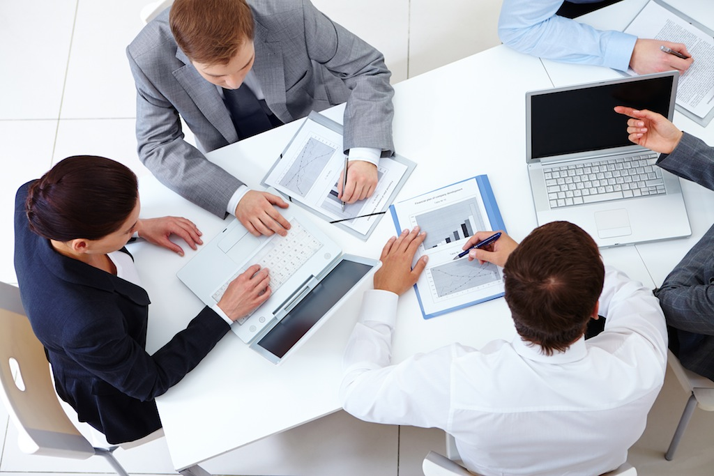 Above view of business team sitting around table and working