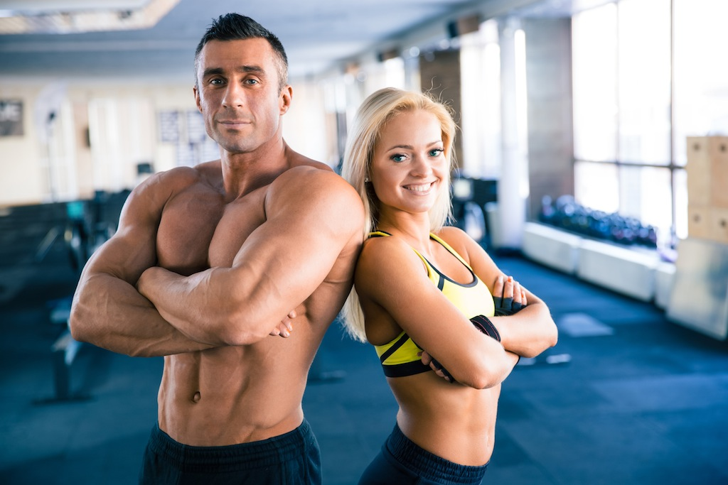 Handsome muscular man and beautiful sporty woman with arms folded standing in gym. Looking at camera