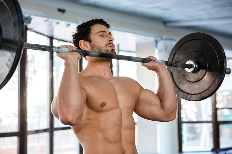 Portrait of a muscular man workout with barbell in gym