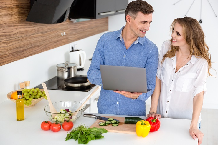 Happy couple using laptop and preparing vegetarian dishes in the kitchen at home