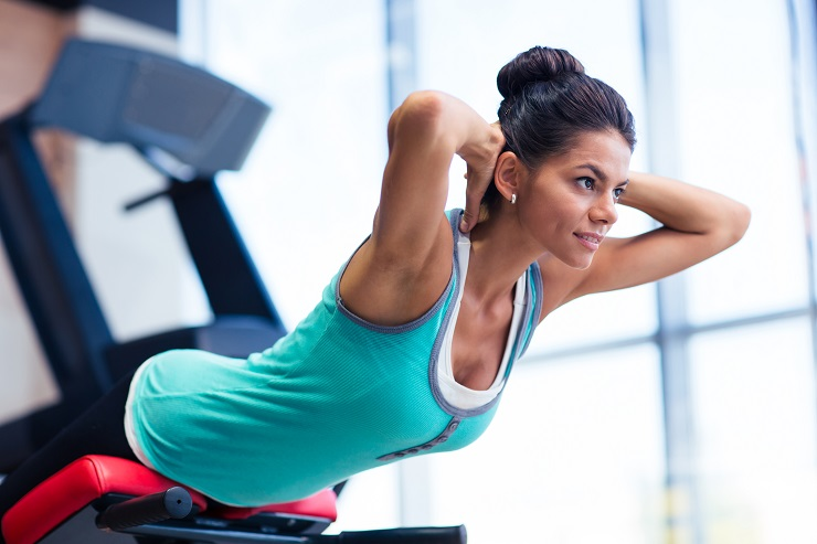 Young pretty woman workout on exercises machine in fitness gym