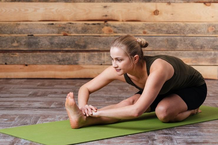 Woman doing yoga exercises on yoga mat
