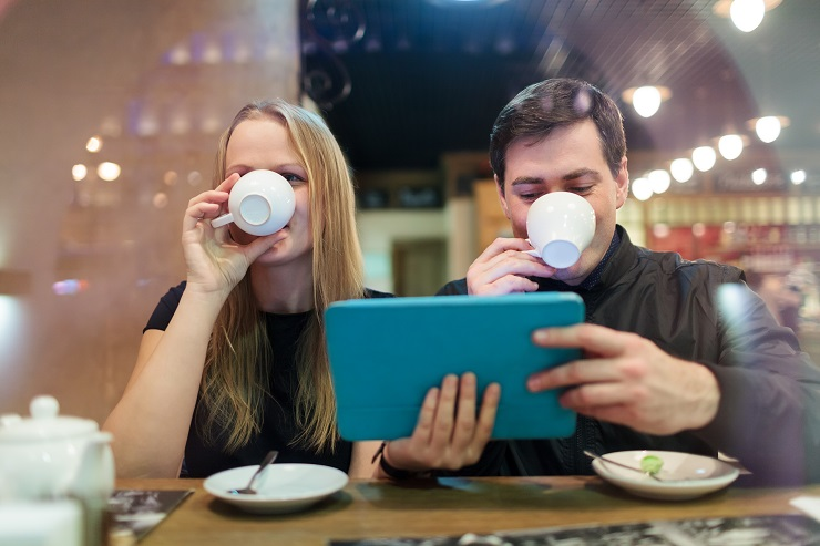 Man and woman drinking coffee while holding a smart tablet