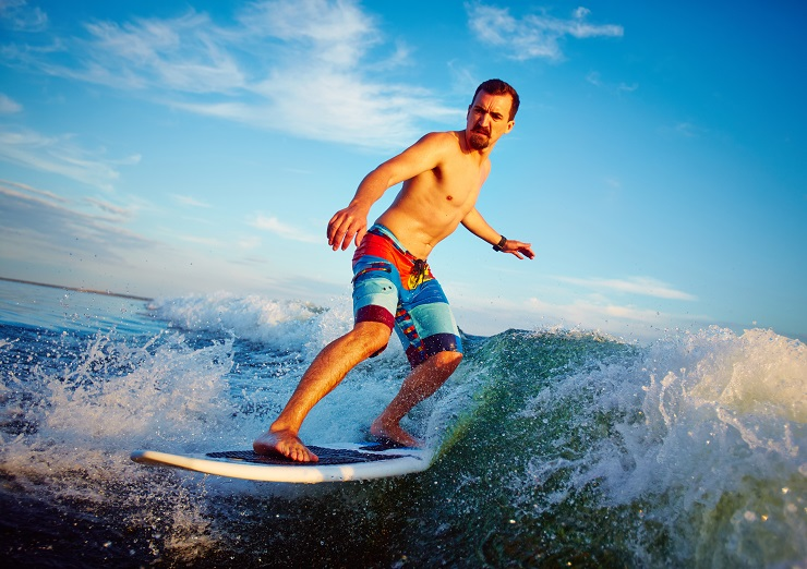 Young man surfboarding in summer
