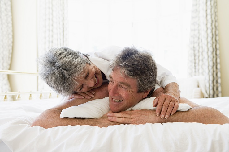 Couple relaxing in bedroom and smiling