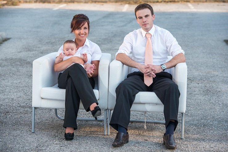 Happy couple with baby sitting in armchairs outside