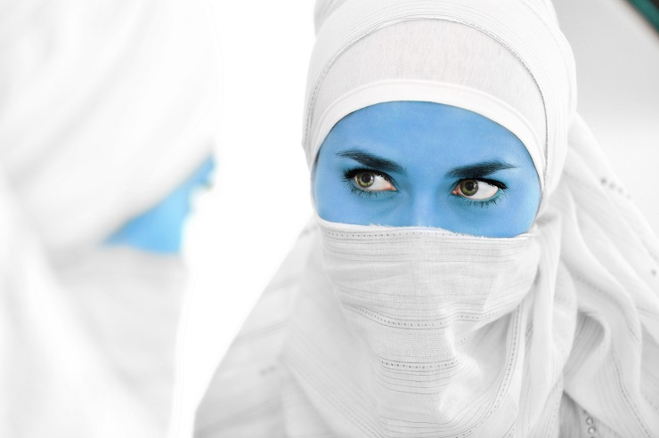Muslim woman with blue skin as alien or avatar looking at mirror, conceptual image