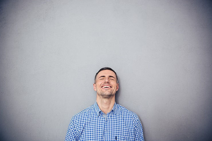 Portrait of a laughing young man over gray background. Leaning on the gray wall