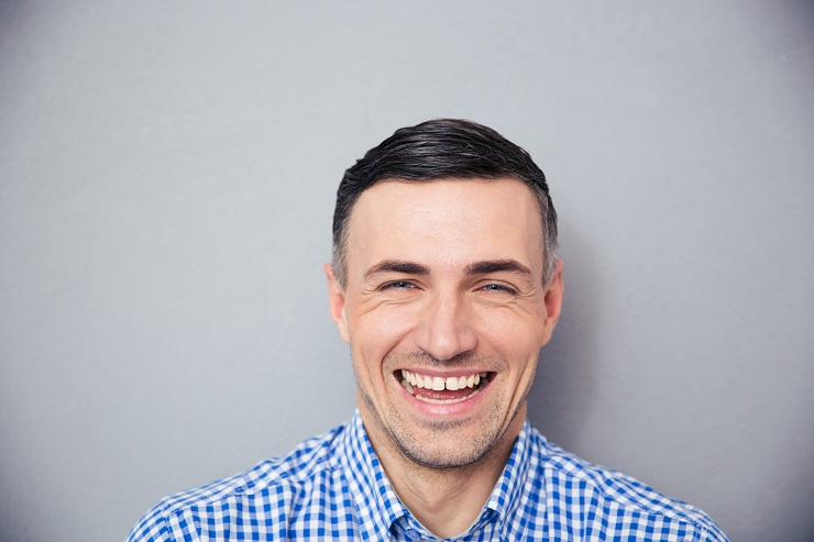 Portrait of a laughing man over gray background. Looking at camera