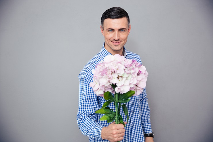 Smiling man holding flowers over gray background and looking at camera