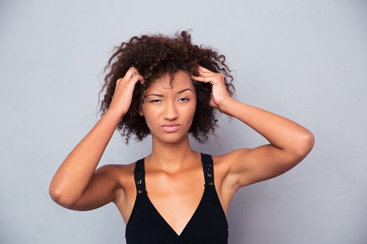 Portrait of a pensive afro american woman looking at camera over gray background