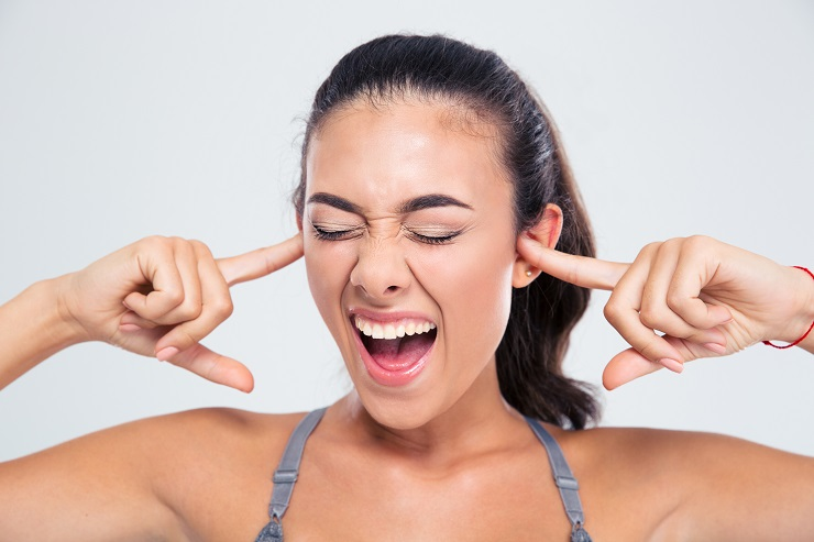 Portrait of a fitness woman covering her ears with fingers and shouting isolated on a white background