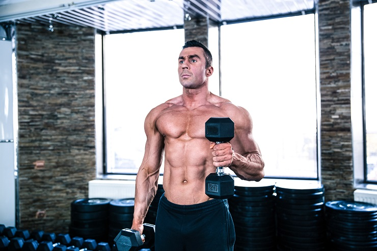 Muscular handsome man workout with dumbbells at gym