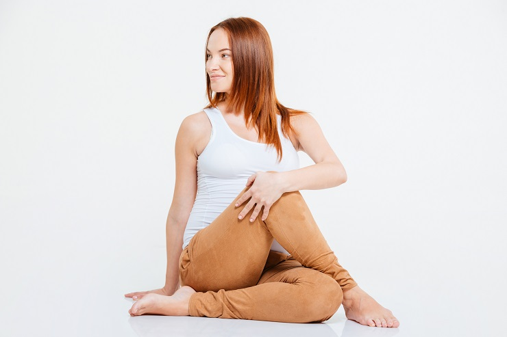 Happy pregnant woman doing yoga exercise on the floor isolated on a white background