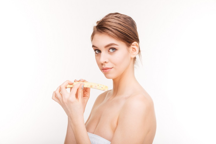 Beauty portrait of pretty young woman filing nails over white background