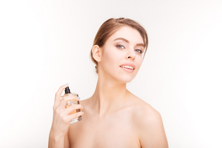 Beauty portrait of attractive young woman applying parfum over white background