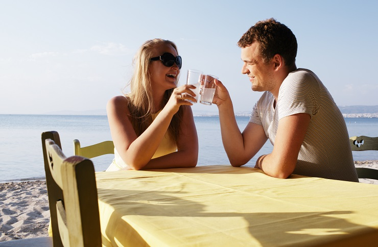 Young couple enjoying drinks at the seaside while on their summer vacation sitting at a table on the beach in the sunshine
