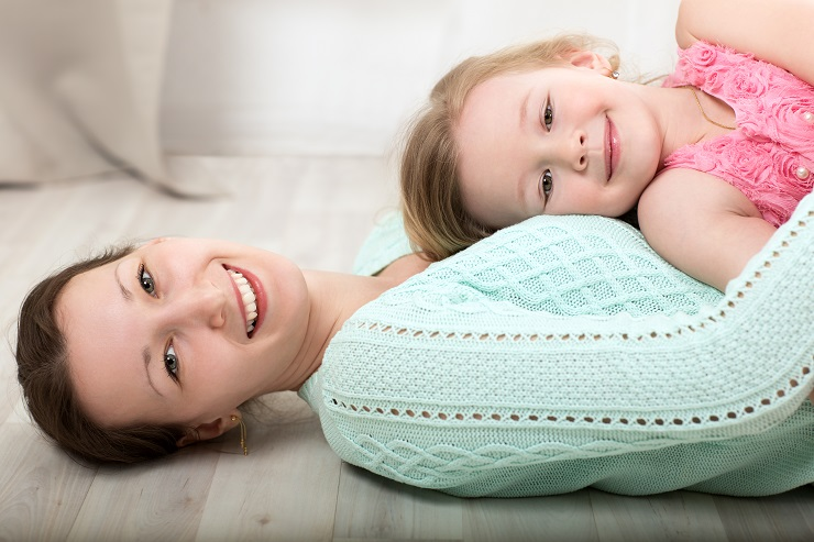 Happy young mother lying on the floor and holding smiling little daughter on the chest