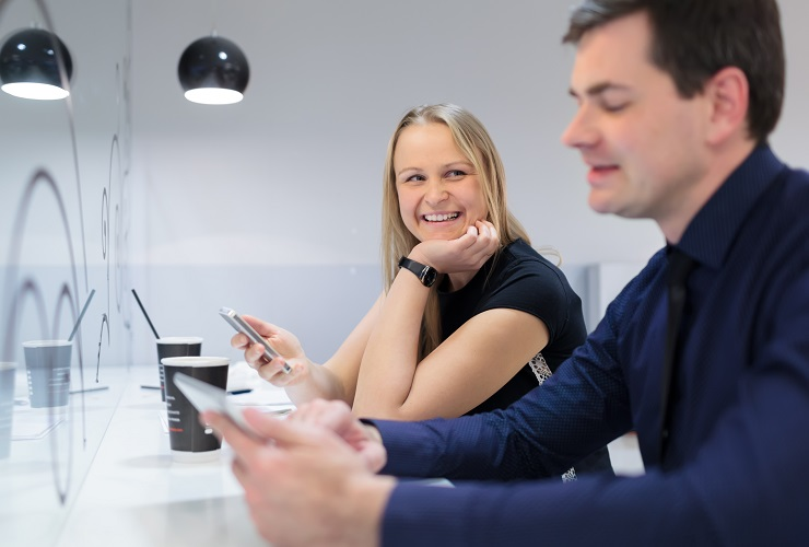 Businessman and woman in a meeting conversing holding their mobile phone and tablet
