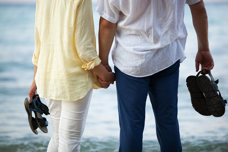 Man and woman standing barefoot by the sea and holding hands. Romantic vacation