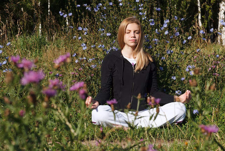 Lotus yoga pose. Woman meditating in the city park at summer morning. Beautiful blue flowers in foreground.
