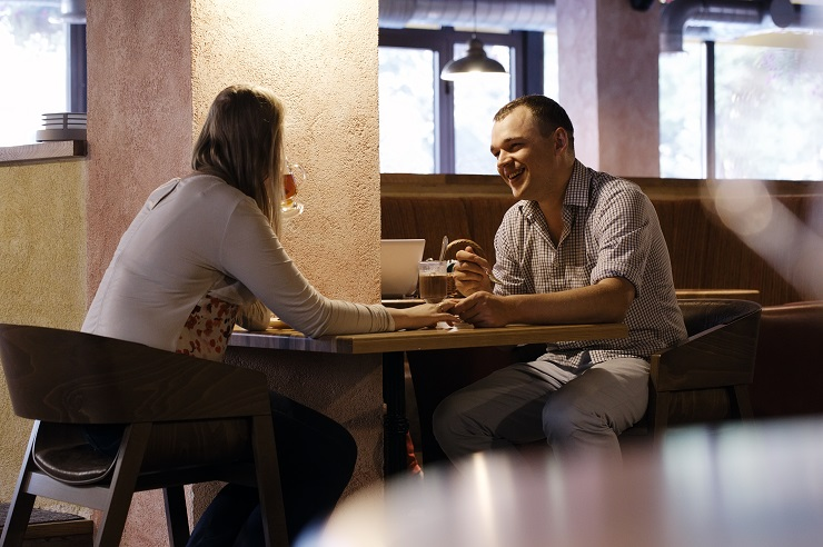Young couple in a cafe having dinner and talking.