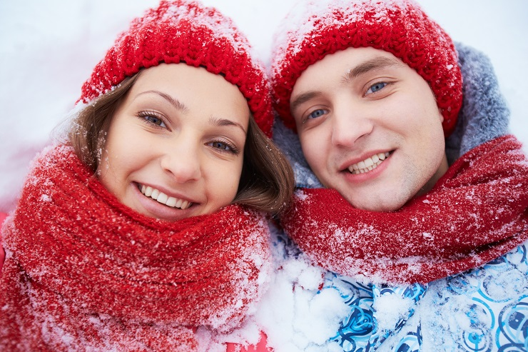 Faces of smiling dates in winterwear looking at camera