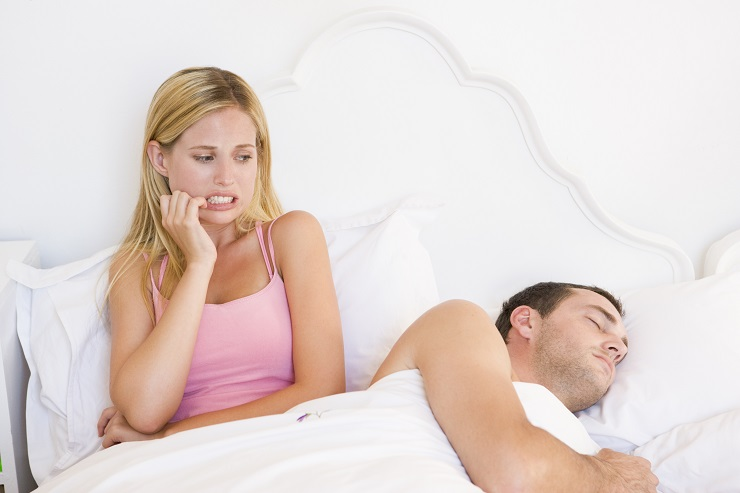 A young couple in bed with the woman looking anxious